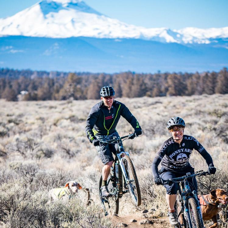 Two mountain bikers in a field outside Bend Oregon