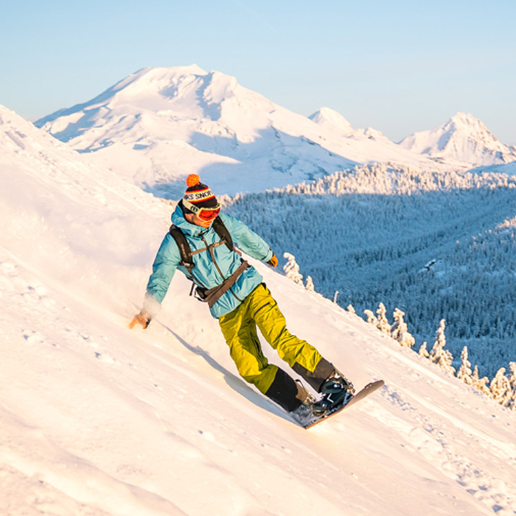 A snowboarder in a blue coat on Mount Bachelor