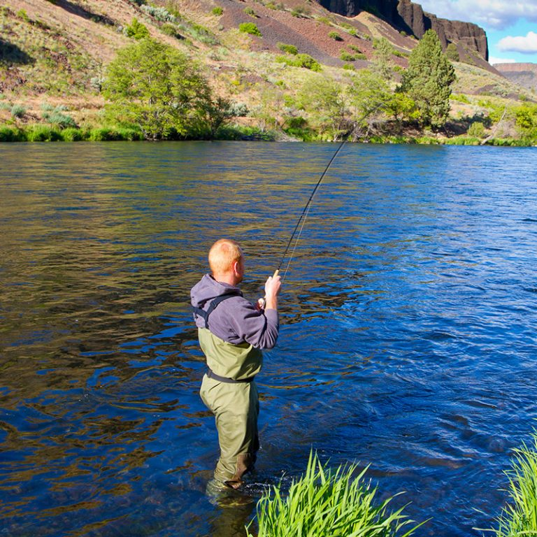 A man in green waders fishing on the Deschutes River